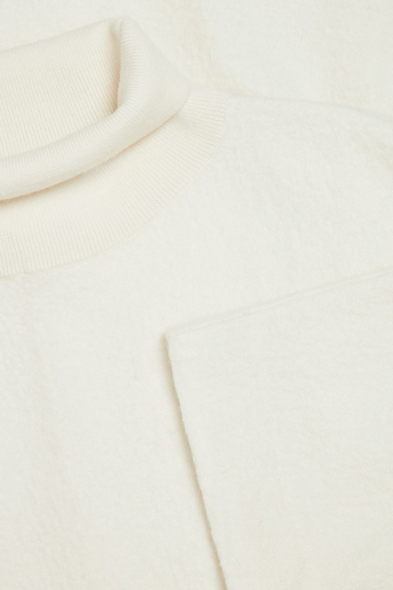 COS 메리노 울 롤넥 니티드 맥시 드레스의 오프 화이트컬러 Detail입니다.