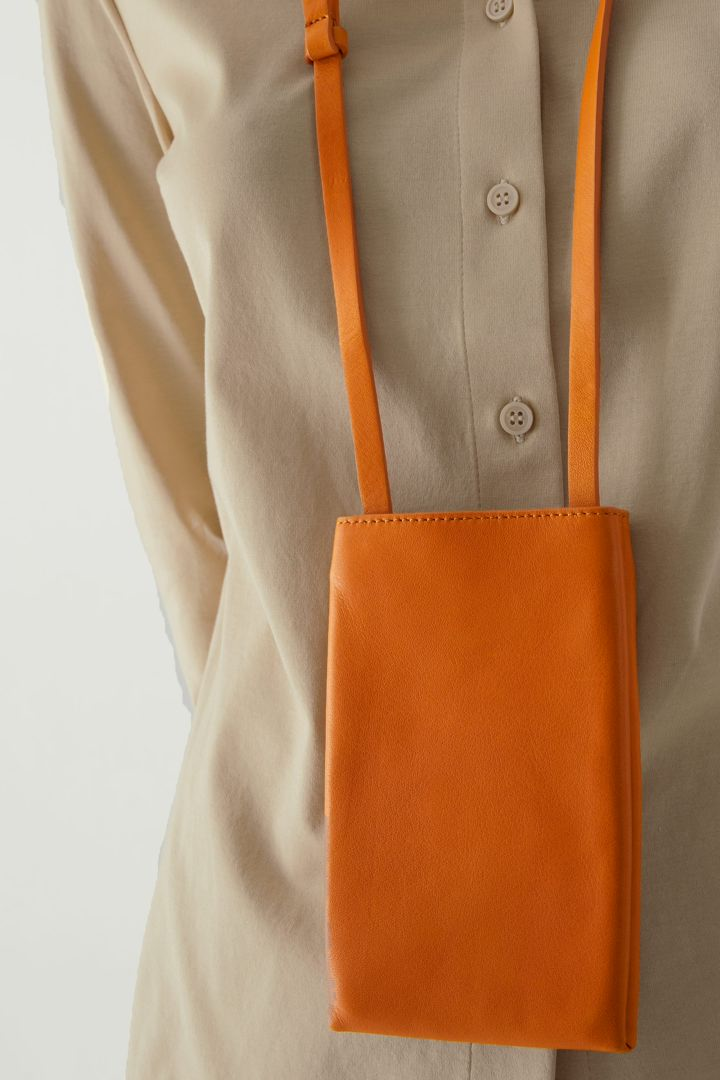 COS 레더 폰 파우치의 오렌지컬러 ECOMLook입니다.
