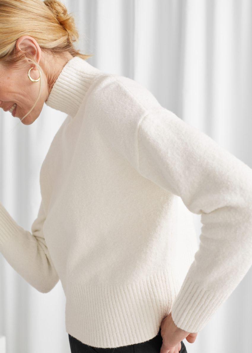 앤아더스토리즈 크롭 모크 넥 스웨터의 화이트컬러 ECOMLook입니다.