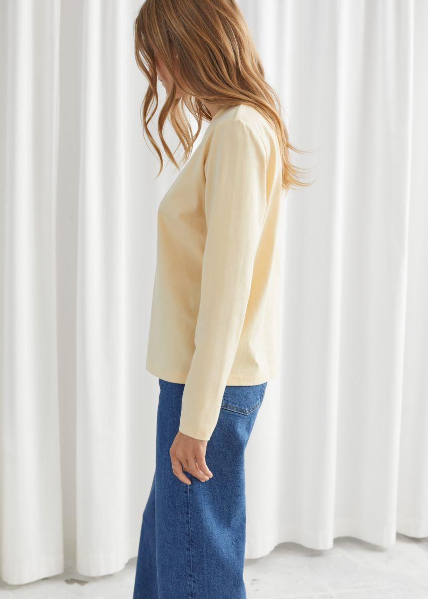 앤아더스토리즈 코튼 롱 슬리브 티셔츠의 라이트 옐로우컬러 ECOMLook입니다.