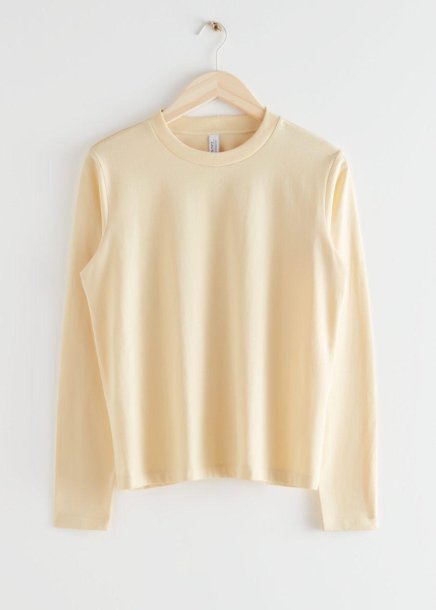 앤아더스토리즈 코튼 롱 슬리브 티셔츠의 라이트 옐로우컬러 Product입니다.