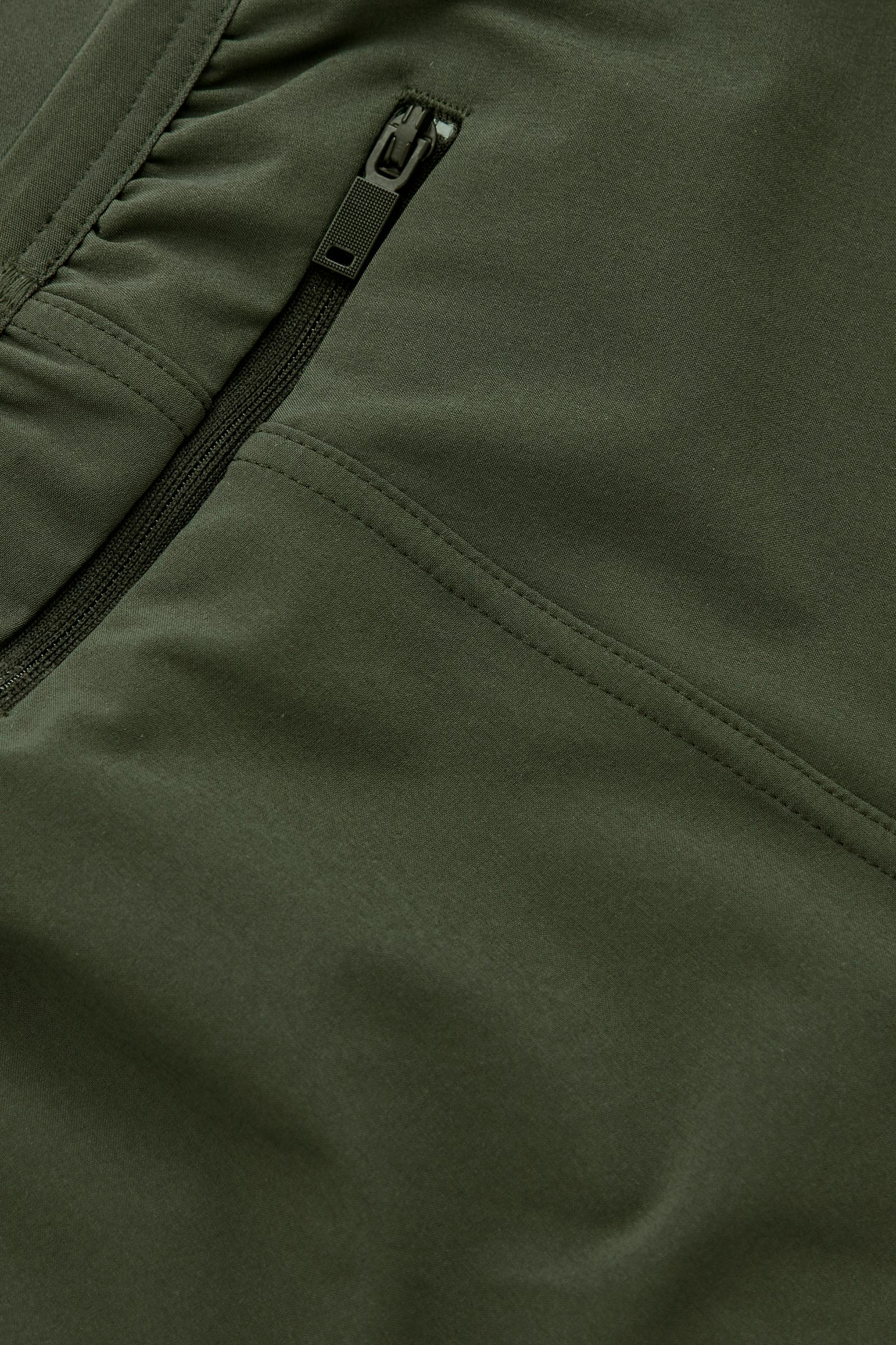 COS 리사이클드 폴리에스터 테이퍼드 러닝 트라우저의 다크 그린컬러 Detail입니다.