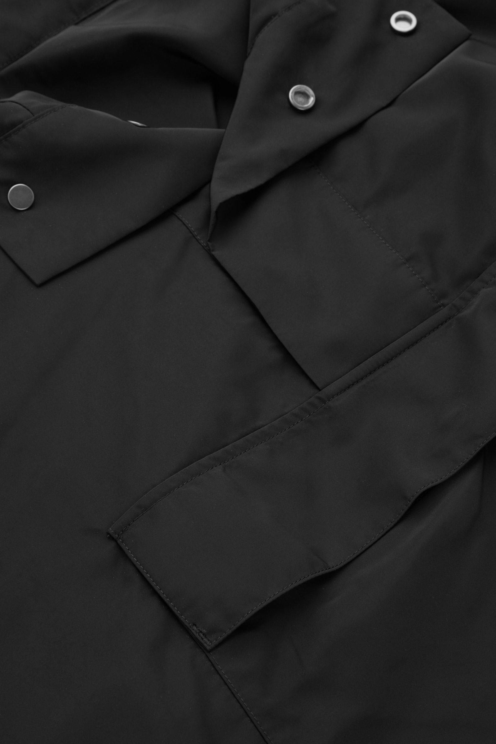 COS 후디드 레인 판초의 블랙컬러 Detail입니다.